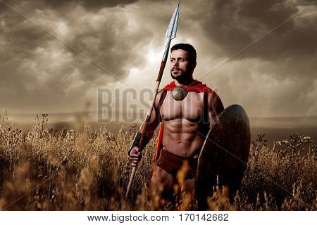 Soldier wearing in armor and red cloak like spartan holding bronze sword. Warrior wearing like antique roman looking away, going in attack at field. Nighttime with dark sky.