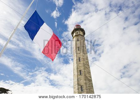view from the ground of the 1854 Grand Phare des Baleines lighthouse with a tricolor French flag floating in the wind in front, Ile de Re, France.
