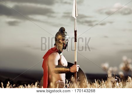 Confident soldier wearing in armor like spartan holding bronze sword. Warrior wearing iron helmet and red cloak like antique roman looking at camera, standing at field. Nighttime with dark sky.
