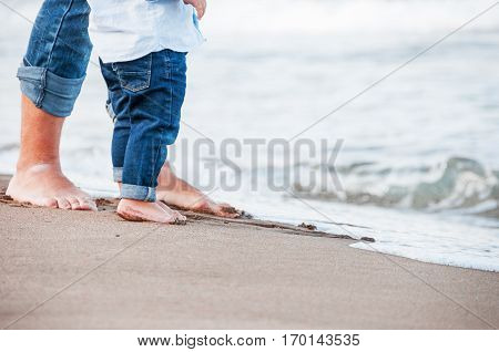 Bare feet of child and adult on the sea. vacation concept. Happy family concept