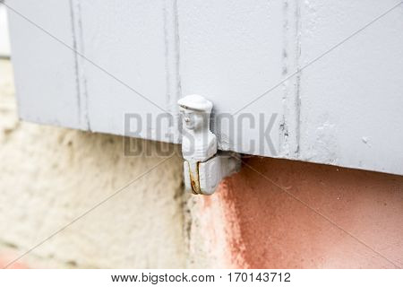 pale blue/grey wooden shutter with vintage shutter swing fastener in shape of a man