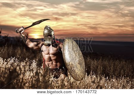 Confident soldier like spartan in red cloak holding iron weapon and rounded shield. Warrior in bronze helmet with bare torso going in attack of war in field. Dark sky at sunset.