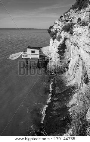 Black and white view of traditional fisherman's wooden hut at the bottom of the limestone cliff in the estuary of Gironde Meschers-sur-Gironde