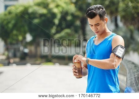 Handsome sporty man looking at fitness tracker and opening sports water bottle while taking short break, waist-up portrait