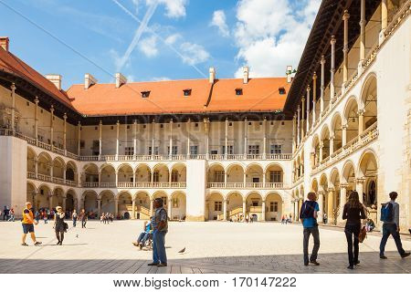 Krakow, Poland - June 08, 2016: Group Of Tourists Looking Around At Central Part Of Well-known Wawel