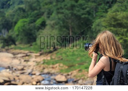 Close-up of cute young female wildlife photographer during safari making photos of landscape