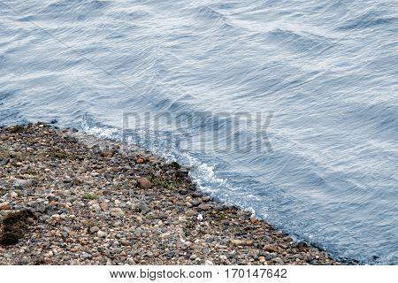 Coast of Siberian river. Stone coast and blue water.