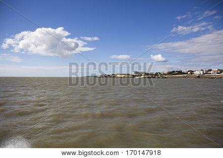 View of the coastline with seaside resort of Royan with blue sky and fluffy white clouds, France