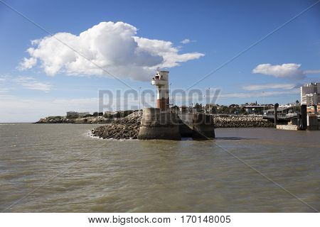 Entrance of port of Royan with small red and white lighthouse France