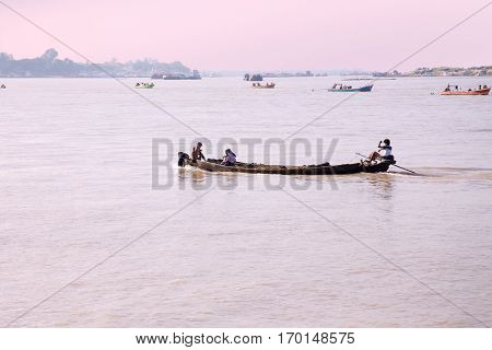 IRRAWADY RIVER, MYANMAR - November 17, 2015: Boats on the Irrawaddy River at sunrise. The Irrawady river  is a river that flows from north to south through Myanmar and is the most important waterway