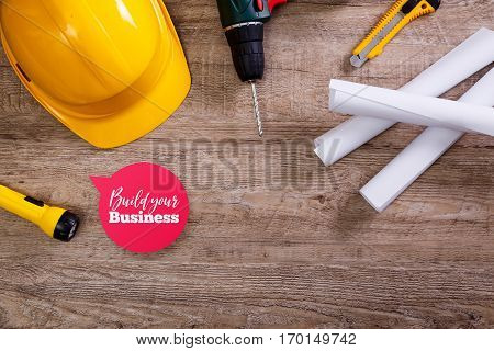 Yellow helmet, drill and flashlight. Build your business speech bubble. Construction concept. Architecture plans and knifes. Worker equipment.