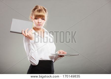 Woman holding ebook reader and book. Choice between modern educational technology and traditional way method. Girl with digital tablet pc and textbook. Contemporary education.