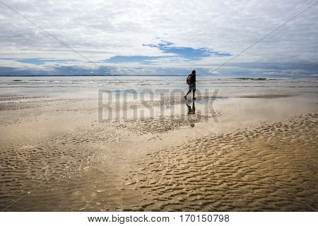 maritime seaside landscape with man walking on the sand garonne estuary near Royan France