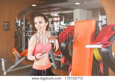 Cheerful beautiful young sportswoman listening to music from mobile phone in gym