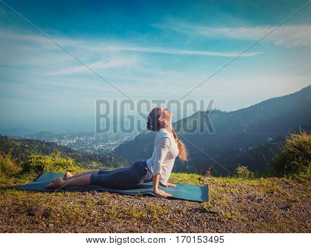 Yoga outdoors - woman practices Ashtanga Vinyasa yoga Surya Namaskar Sun Salutation asana Urdhva Mukha Svanasana - upward facing dog pose in mountains in morning. Vintage retro hipster style image.