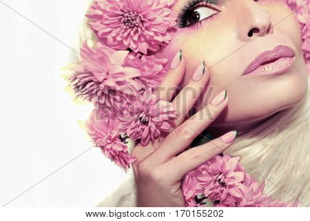 Pastel pink manicure and makeup on a woman with flowers on white background isolated.