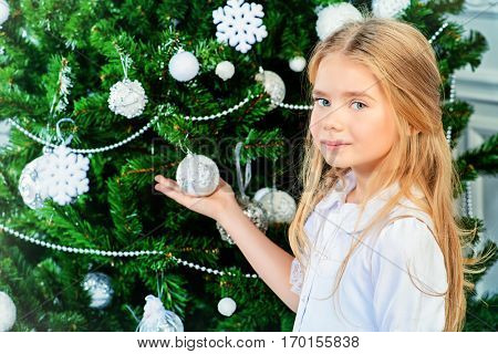 Happy little girl in a beautiful white dress decorates the Christmas tree. Merry Christmas.