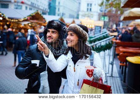 Happy young couple shopping on the street at christmas market, smiling, drinking hot drinks.