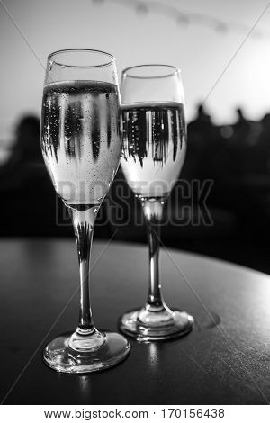 Party and celebration time with champagne flutes in the sunset light, black and white caption