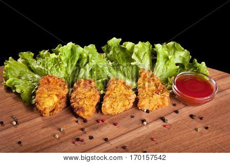 Chicken nuggets on a wooden table with sauce and lettuce on black background.