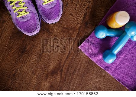 Fitness gym equipment. Sneakers, dumbbells with towel. Orange juice drink. Workout footwear. Sport trainers on grunge rustic wood background.
