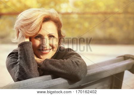 Gorgeous middle aged woman sitting on bench in autumn park