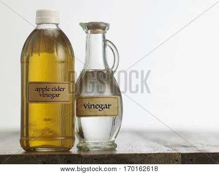 Apple cider vinegar and white vinegar on the wooden table top