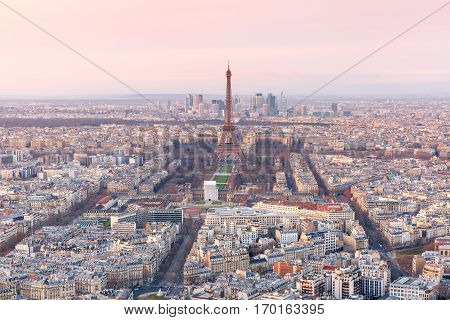 Aerial view of Paris skyline with Eiffel Tower, Les Invalides and business district of Defense at pink sunset, as seen from Montparnasse Tower, Paris, France