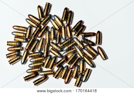 Close up of 9 mm. bullets with 9 mm. handgun in background