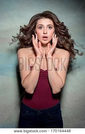 Portrait of young woman with shocked and surprised facial expression on gray studio background