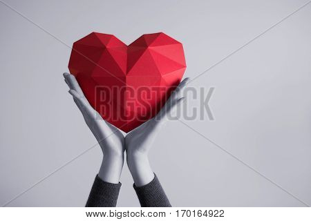 Two female hands holding red polygonal paper heart shape. Tonned image