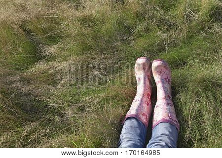 Low section of woman wearing pink galoshes lying on grass at field