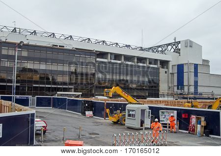 LONDON UK - SEPTEMBEr 17 2016: Workmen standing outside the main entrance for construction workers at the rebuilding of the famous White Hart Lane stadium in Tottenham North London. Home to the renowned football club Tottenham Hotspur.