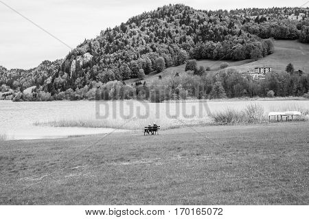 Black and white landscape of the Brenet Lake and Jura mountain with couple of old man and woman sitting on a bench and feeding a swan Le Pont Switzerland