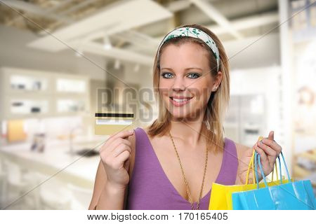 Young woman holding a credit card and shopping bags inside a mall