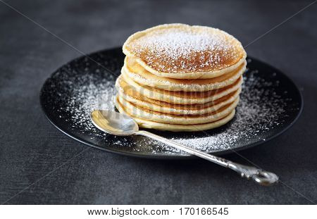 Pancakes with icing sugar on the dark background