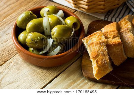 Jumbo gordal olives with herbs and onions rustic baguette on wood background