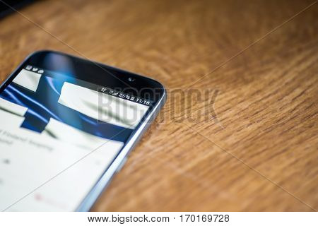 Smartphone On Wooden Background With 5G Network Sign 25 Per Cent Charge And Finland Flag On The Scre
