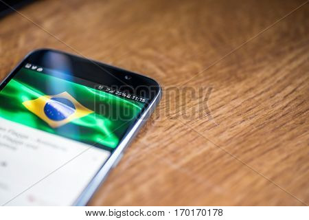Smartphone On Wooden Background With 5G Network Sign 25 Per Cent Charge And Brazil Flag On The Scree