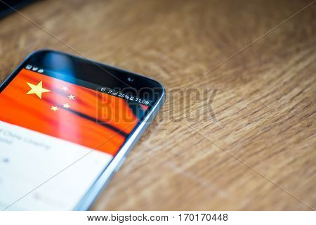 Smartphone On Wooden Background With 5G Network Sign 25 Per Cent Charge And China Flag On The Screen