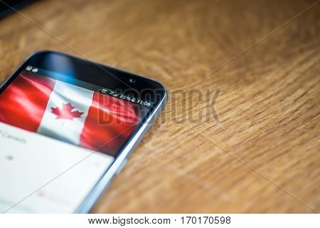 Smartphone On Wooden Background With 5G Network Sign 25 Per Cent Charge And Canada Flag On The Scree