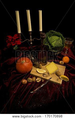 Old style still life with candles pumkin cheese cabbage likor bottle lemon slices with black background