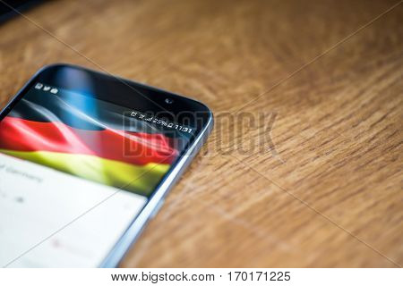 Smartphone On Wooden Background With 5G Network Sign 25 Per Cent Charge And German Flag On The Scree