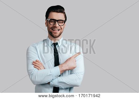 Pointing copy space. Handsome smiling man in eyeglasses keeping arms crossed and looking at camera while standing against grey background