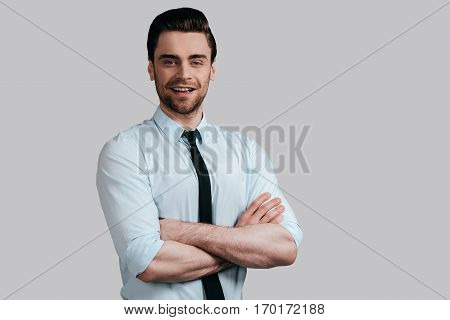 Confidence and charisma. Handsome young smiling man in white shirt and tie keeping arms crossed and looking at camera while standing against grey background