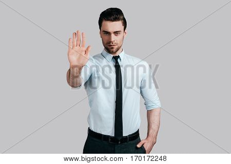 No way to cheat him! Serious young man in white shirt and tie gesturing and looking at camera while standing against grey background