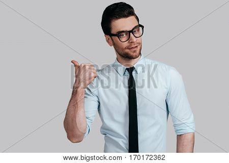 Pointing copy space. Handsome young man looking at camera and pointing away while standing against grey background