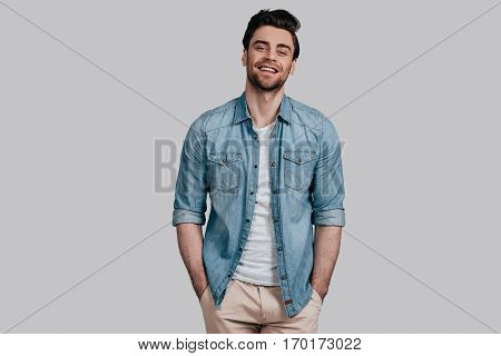 Perfect man. Handsome young man in blue jeans shirt keeping hands in pockets and looking at camera while standing against grey background