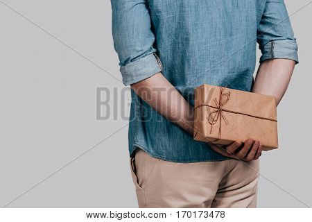 Surprising her... Close-up rear view of man in blue jeans shirt holding a gift box behind his back while standing against grey background