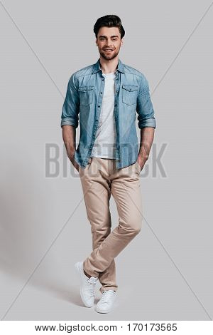 Confident and handsome. Full length of good looking young man in casual wear keeping hands in pockets and smiling while standing against grey background